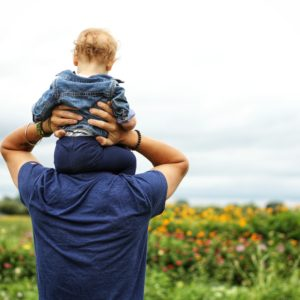 father and son staring into the field image