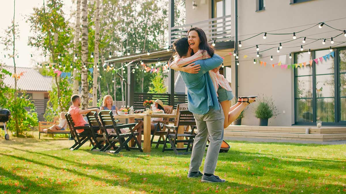 happy couple celebrating with a hug during a summer family bar-b-q