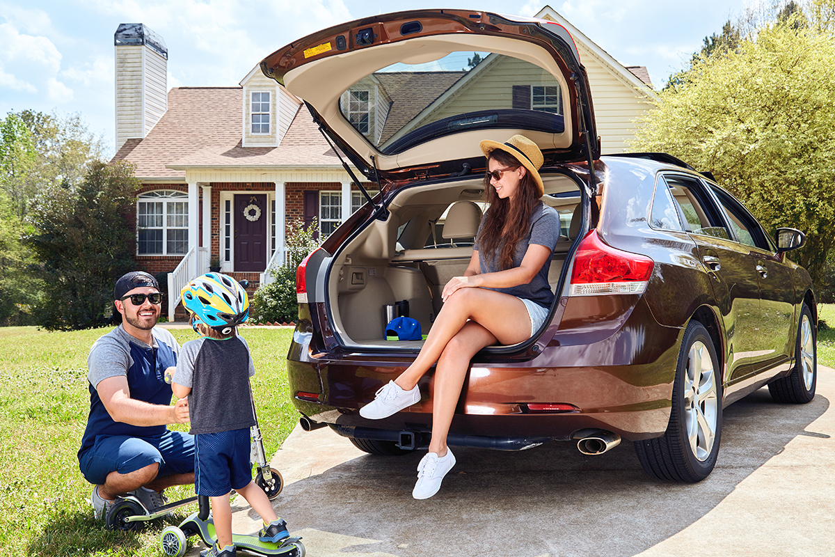 Family in the back of their car in front of their home