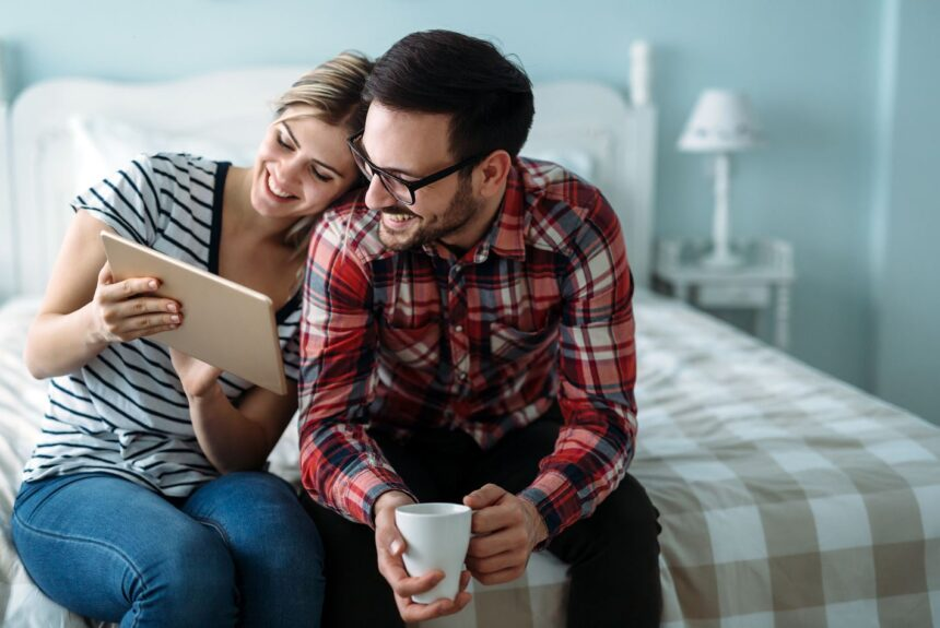 happy couple looking at a tablet together at home